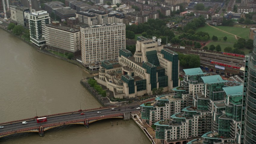 6K stock footage aerial video of orbiting the MI6 Building revealing skyscraper in the rain, London, England Aerial Stock Footage | AX115_069