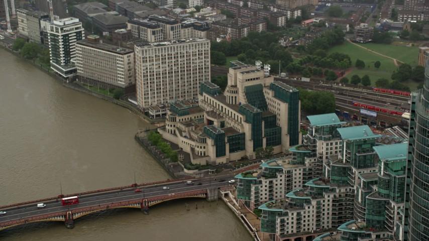 6K aerial video of orbiting the MI6 Building revealing skyscraper in the rain, London, England Aerial Stock Footage | AX115_069