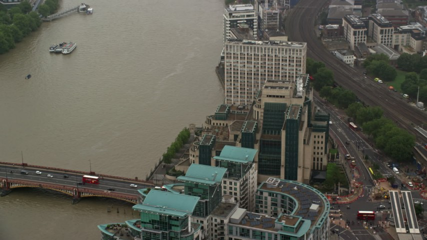 6K stock footage aerial video of orbiting MI6 Building beside River Thames in the rain, London, England Aerial Stock Footage | AX115_070