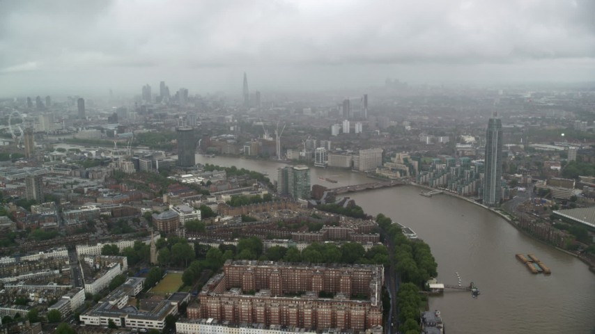 6K stock footage aerial video of River Thames winding through the city while raining, London, England Aerial Stock Footage | AX115_083