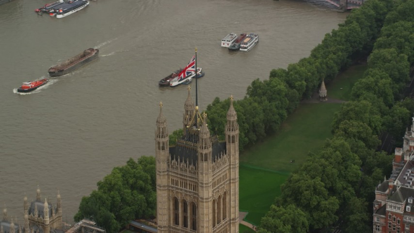 6K stock footage aerial video of British Flag atop Parliament beside River Thames, London England Aerial Stock Footage | AX115_100