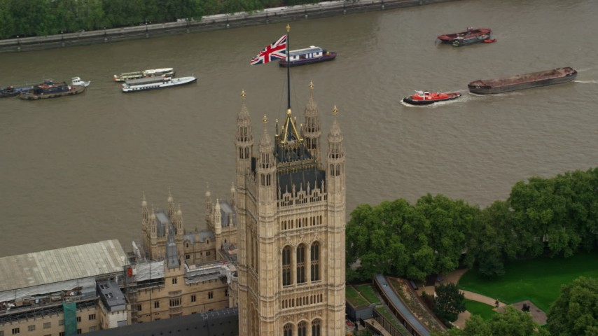 6K stock footage aerial video of orbiting British Flag atop Parliament along River Thames, London England Aerial Stock Footage | AX115_101