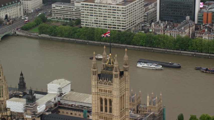 6K stock footage aerial video of an orbit of the British Flag on Parliament along River Thames, London England Aerial Stock Footage | AX115_102