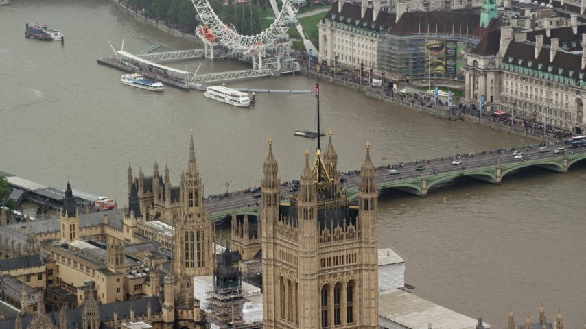 British Flag atop Parliament reveal Big Ben, London England Aerial Stock Footage | AX115_103