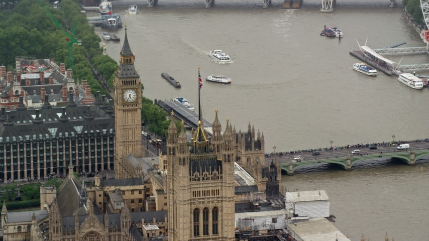 British Flag atop Parliament and Big Ben, London England Aerial Stock Footage | AX115_104