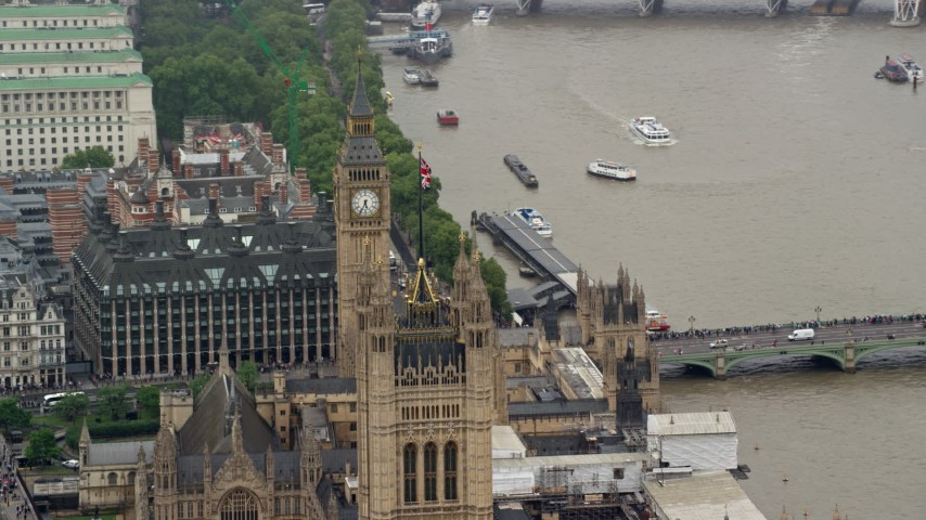 6K stock footage aerial video of the British flag atop Parliament, and Big Ben, London, England Aerial Stock Footage | AX115_104