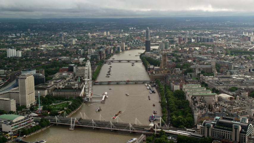 6K stock footage aerial video of bridges spanning the River Thames through the city by London Eye and Parliament, England Aerial Stock Footage | AX115_120