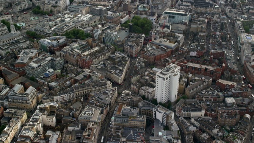 6K stock footage aerial video of orbiting city buildings around Long Acre and Charing Cross Road intersection, London, England Aerial Stock Footage | AX115_208