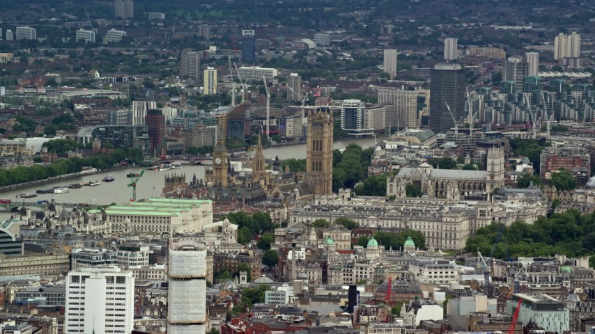 6K stock footage aerial video of Big Ben and Parliament among city buildings, London, England Aerial Stock Footage | AX115_239