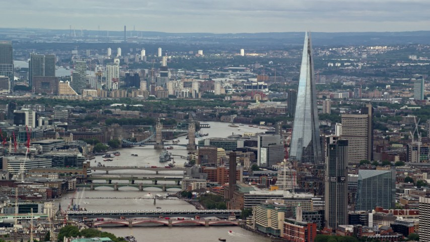 6K stock footage aerial video of The Shard and Tower Bridge spanning the Thames, reveal Canary Wharf, London, England Aerial Stock Footage | AX115_247