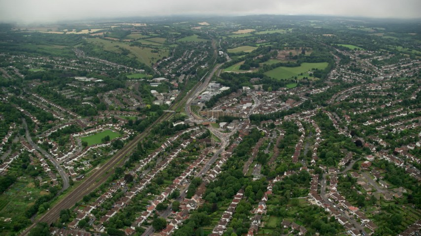 6K stock footage aerial video of flying over suburban homes near railroad tracks, Purley, England Aerial Stock Footage | AX115_299