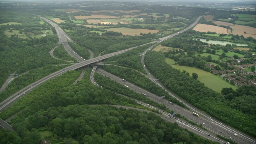 6K stock footage aerial video of orbiting trees around the M23 and M25  freeway interchange, Redhill, England