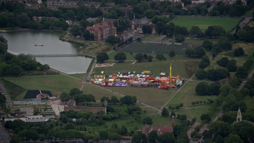 6K stock footage aerial video of flying by small fair at Burgess Park, London, England, twilight Aerial Stock Footage | AX116_007