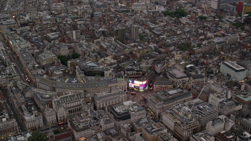 6K stock footage aerial video of orbiting Piccadilly Circus in London, England, twilight Aerial Stock Footage AX116_034 | Axiom Images