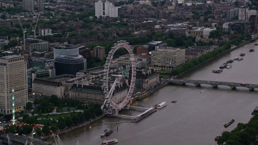 6K stock footage aerial video of flying by the London Eye by River Thames, London, England, twilight Aerial Stock Footage | AX116_058
