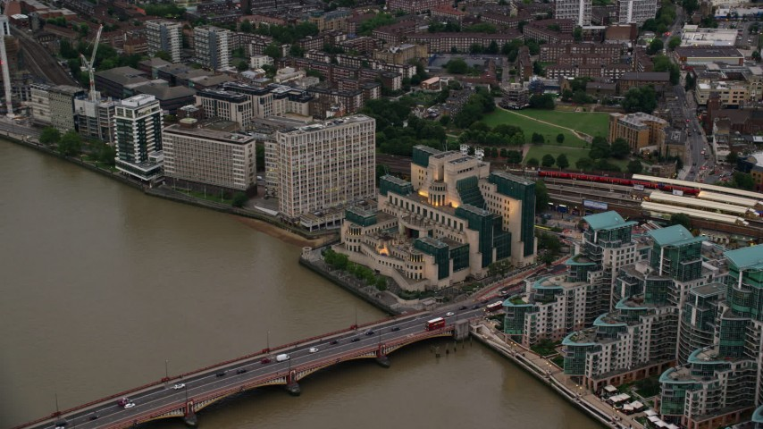 6K stock footage aerial video reverse view of MI6 Building, revealing St George Wharf, London, England, twilight Aerial Stock Footage | AX116_068