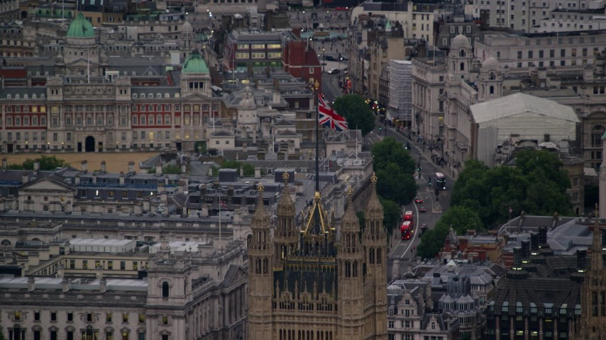 6K stock footage aerial video of the British Flag atop the British Parliament, London, England, twilight Aerial Stock Footage | AX116_072