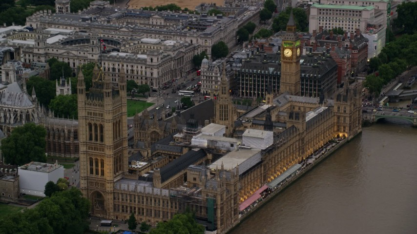 6K stock footage aerial video of approaching Big Ben and British Parliament, seen from the river, London, England, twilight Aerial Stock Footage | AX116_074