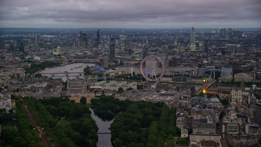 6K stock footage aerial video skyscrapers seen from near London Eye and Big Ben by River Thames, London, England, night Aerial Stock Footage AX116_115 | Axiom Images