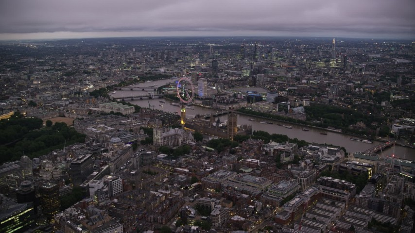6K stock footage aerial video approach Big Ben, British Parliament, London Eye, and Westminster Abbey, London, England, night Aerial Stock Footage AX116_140 | Axiom Images