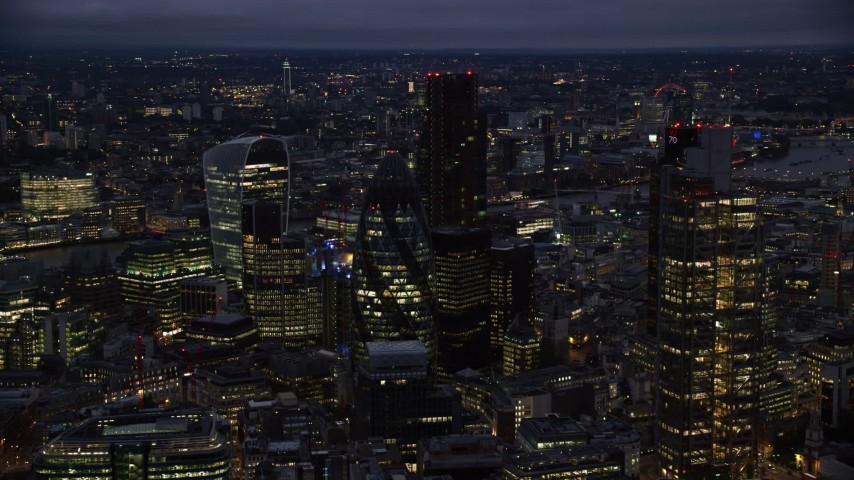 6K stock footage aerial video of The Gherkin skyscraper, seen from near Heron Tower, London, England, night Aerial Stock Footage | AX116_166