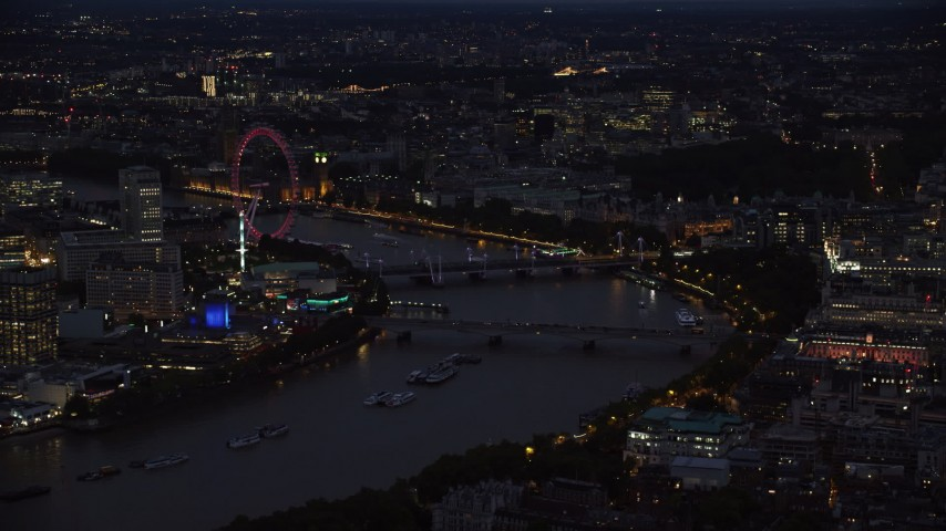 6K stock footage aerial video of an approach to London Eye by bridges over River Thames, London, England, night Aerial Stock Footage | AX116_175