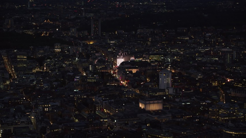 6K stock footage aerial video of flying over city buildings to approach Piccadilly Circus, London, England, night Aerial Stock Footage | AX116_176