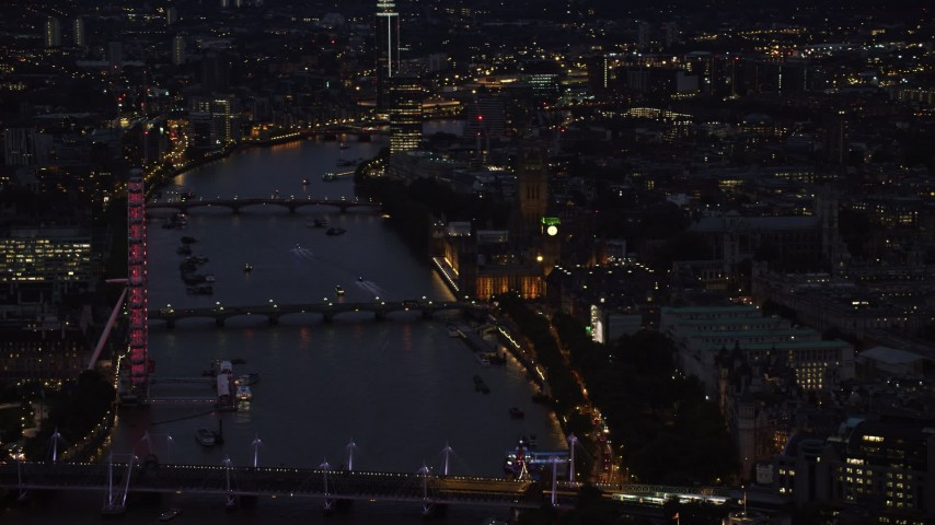 6K aerial video passing by London Eye, Big Ben and Parliament, and River Thames bridges, London, England, night Aerial Stock Footage | AX116_178