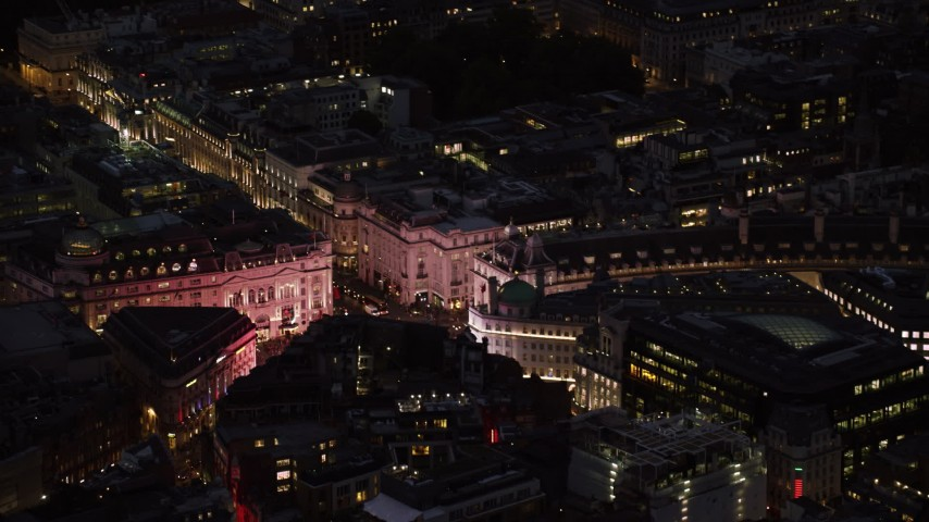6K stock footage aerial video of flying by the bright lights of Piccadilly Circus, London, England, night Aerial Stock Footage | AX116_180