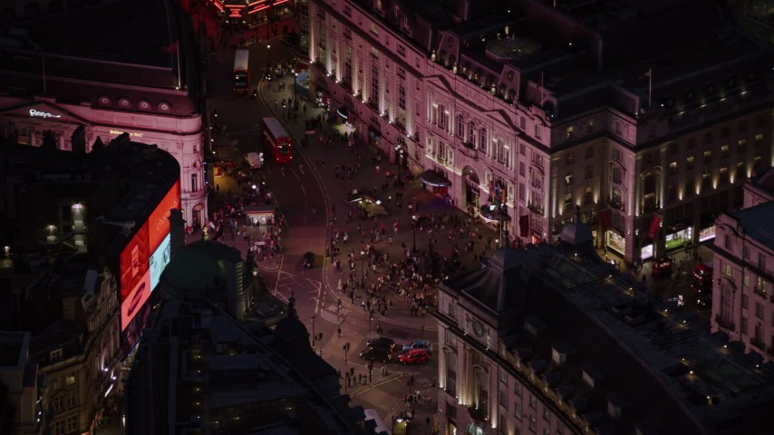 6K stock footage aerial video flying by crowds and double decker buses at Piccadilly Circus, London, England, night Aerial Stock Footage | AX116_182
