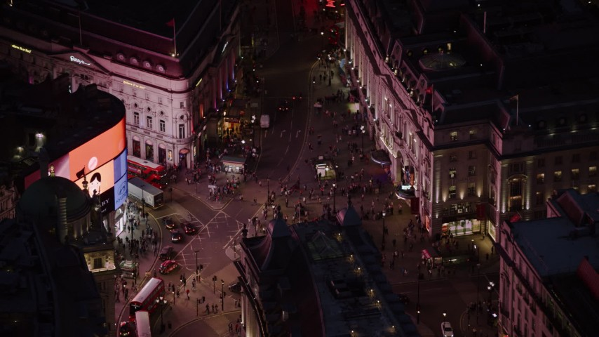 6K stock footage aerial video of orbiting crowds and double decker buses at Piccadilly Circus, London, England, night Aerial Stock Footage | AX116_183