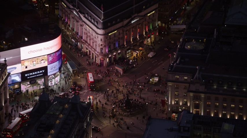 6K stock footage aerial video orbit crowds and double decker buses at Piccadilly Circus, London, England, night Aerial Stock Footage | AX116_184