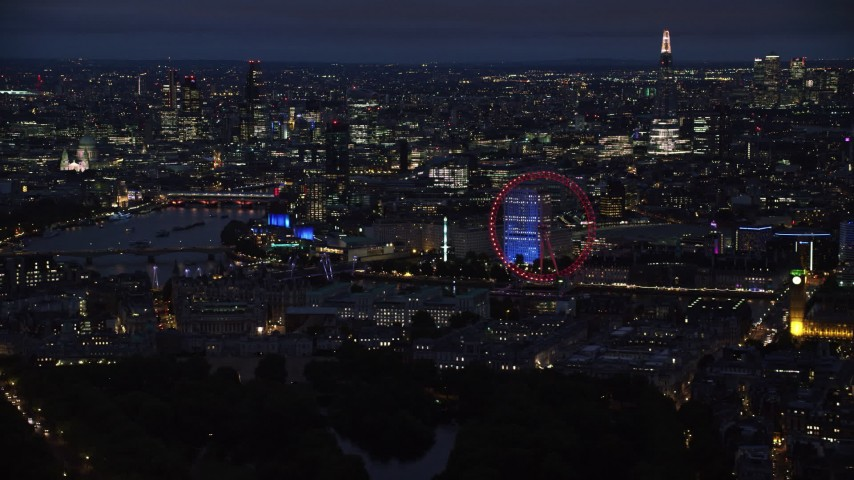 6K aerial video of passing cityscape, London Eye and Big Ben by River Thames, London, England, night Aerial Stock Footage AX116_193