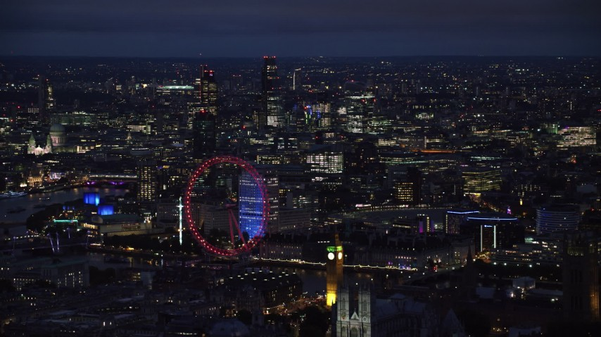6K stock footage aerial video of the London Eye, Big Ben and distant skyscrapers, London, England, night Aerial Stock Footage | AX116_195