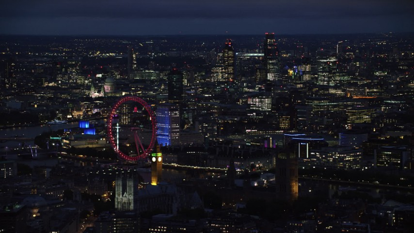 6K stock footage aerial video of London Eye, Big Ben and skyscrapers in the background, London, England, night Aerial Stock Footage AX116_196 | Axiom Images