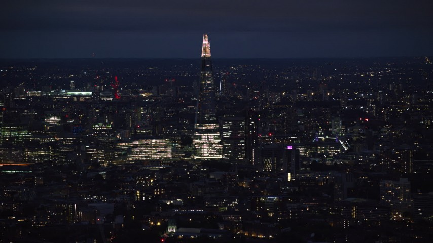 6K stock footage aerial video of The Shard towering over city buildings, London, England, night Aerial Stock Footage | AX116_198