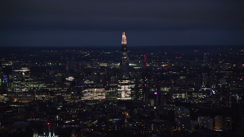 6K stock footage aerial video of a view of The Shard towering over city buildings, London, England, night Aerial Stock Footage | AX116_199