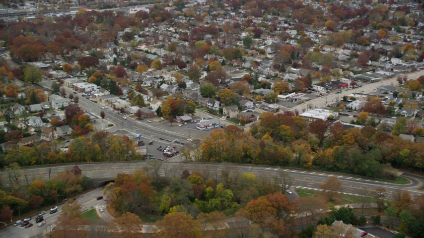 6K stock footage aerial video of shops and suburban homes in Autumn, Wantagh, New York Aerial Stock Footage | AX117_046