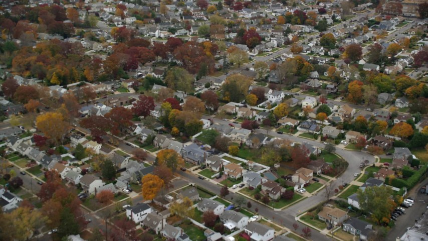 6K stock footage aerial video of flying over suburban neighborhoods in Autumn, Wantagh, New York Aerial Stock Footage | AX117_048