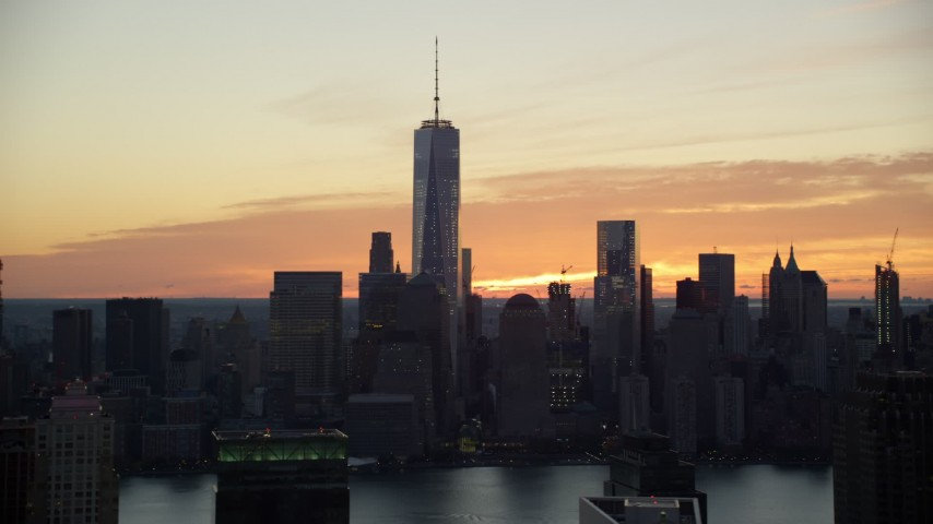 5.5K stock footage aerial video of tall World Trade Center skyscrapers at sunrise seen from Jersey City, Lower Manhattan, New York City Aerial Stock Footage | AX118_033E