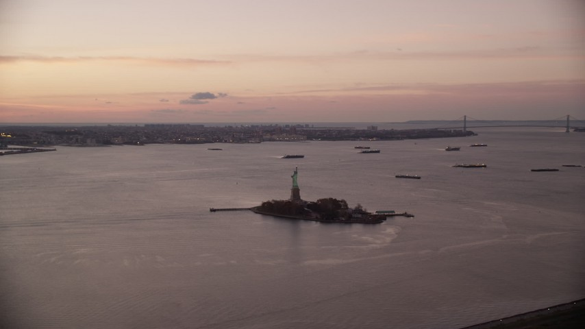 6K stock footage aerial video orbit Statue of Liberty near ships in New York Harbor at sunrise Aerial Stock Footage | AX118_037
