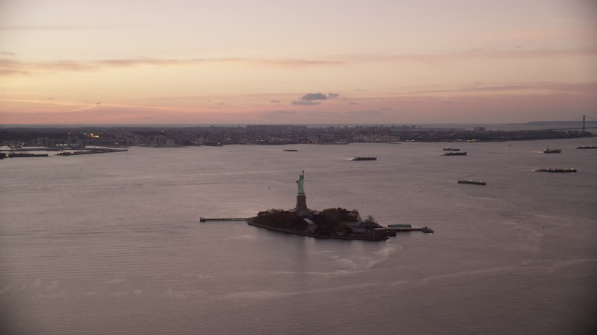 6K stock footage aerial video of the Statue of Liberty at sunrise, New York Aerial Stock Footage | AX118_038