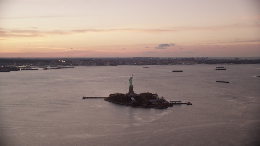 6K stock footage aerial video of a wide view of the Statue of Liberty at sunrise, New York Aerial Stock Footage | AX118_039