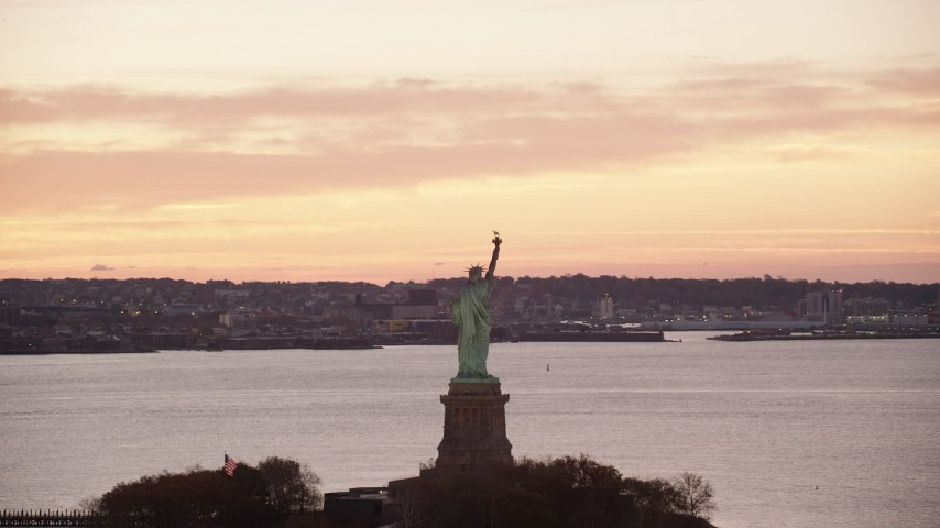 6K stock footage aerial video of orbiting the Statue of Liberty at sunrise, New York Aerial Stock Footage | AX118_041