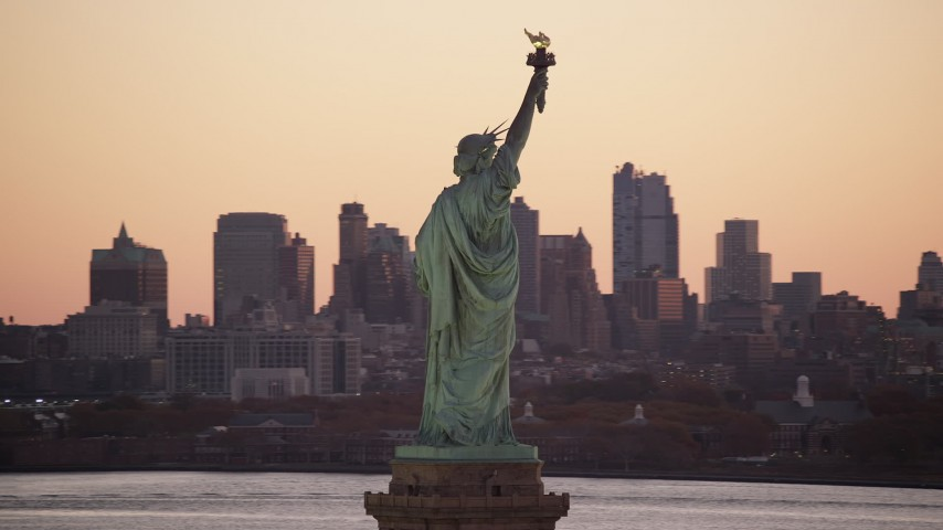 6K stock footage aerial video of orbiting the back of the Statue of Liberty at sunrise, New York Aerial Stock Footage | AX118_043