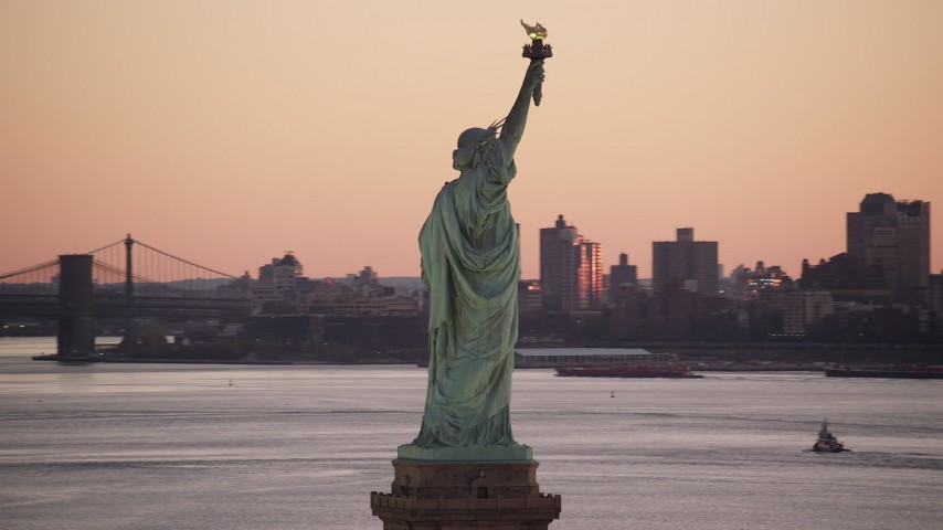 6K aerial video of an orbit of the Statue of Liberty at sunrise, New York Aerial Stock Footage AX118_044
