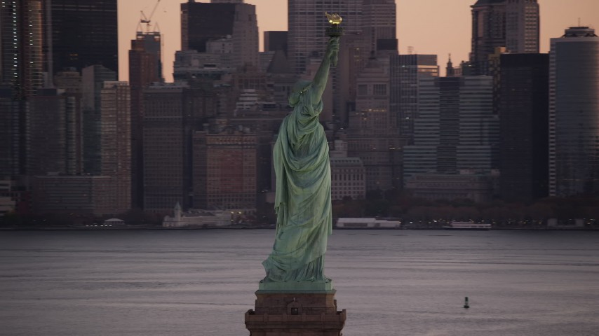 6K aerial video orbit the side of the Statue of Liberty at sunrise, New York Aerial Stock Footage | AX118_045