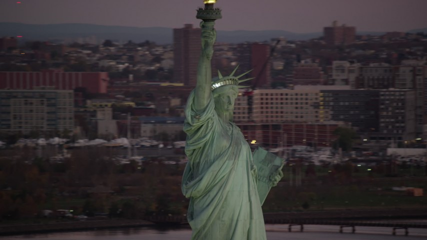 6K stock footage aerial video orbit Statue of Liberty at sunrise, New Jersey in background Aerial Stock Footage | AX118_047