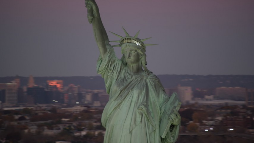 6K stock footage aerial video of an orbit around the front of the Statue of Liberty at sunrise, New York Aerial Stock Footage | AX118_049