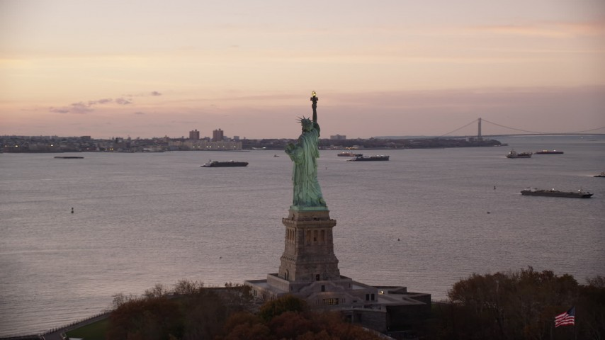 6K aerial video orbit behind the Statue of Liberty at sunrise, New York Aerial Stock Footage | AX118_053